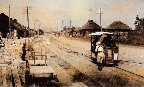 出荷を待つ大谷石と人車貨車の脇を、車夫に押されて人車客車が宇都宮市街地方面に向かう。